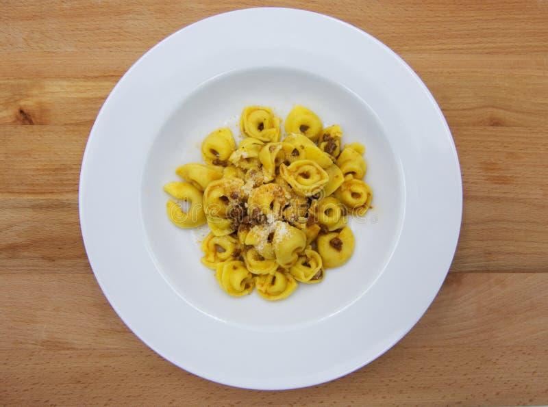 Tortellini με το κρέας στα παραδοσιακά ιταλικά ζυμαρικά ¹ Al ragà Tortellini σάλτσας ντοματών στο ξύλινο υπόβαθρο στοκ φωτογραφία