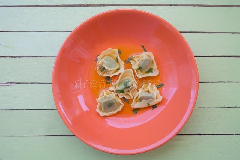 Tortellini in brodo sul piatto arancio su legno verde osservato da sopra fotografia stock libera da diritti