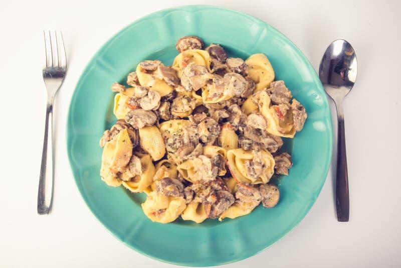 Tortellini com cogumelos em uma placa imagens de stock royalty free