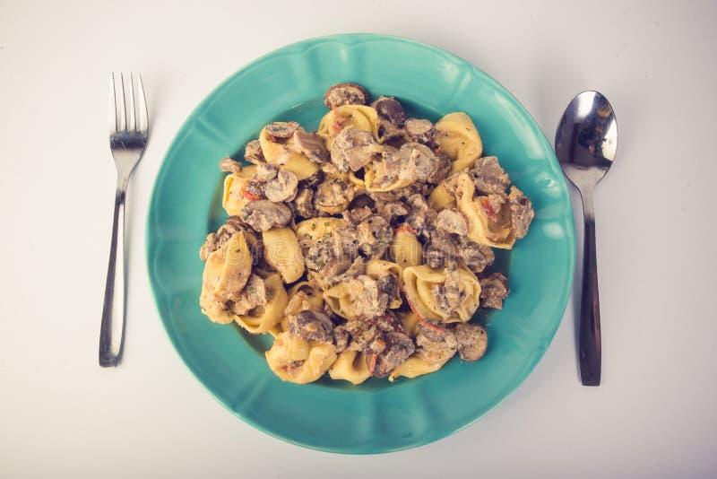 Tortellini com cogumelos em uma placa fotografia de stock