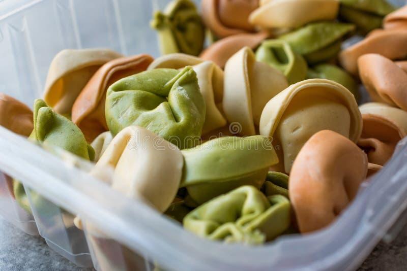 Tortellini crudi colorati della pasta in scatola di plastica multicolore/variopinta o tri colorati fotografie stock