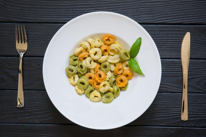 Tortellini pasta with basil leaf on served table with fork and k stock photography