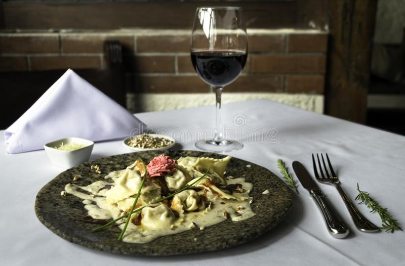 Tortellini pasta with white sauce served on a marble plate with a glass of wine and cuttery. royalty free stock photo