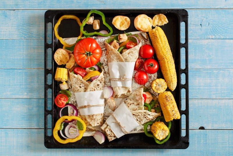 Tortiglia casalinga sullo strato di cottura con le verdure arrostite immagini stock libere da diritti