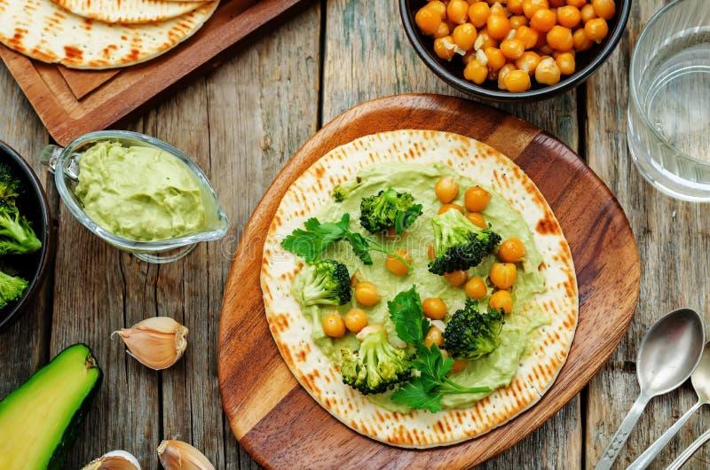 Tortiglia del vegano con i broccoli e ceci ed avocado arrostiti s immagini stock