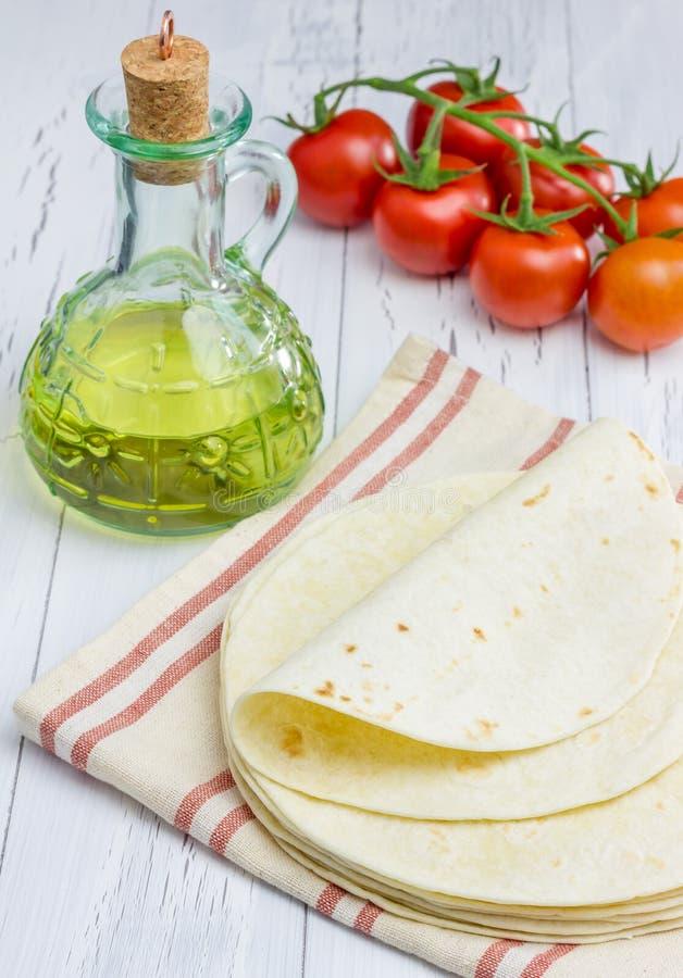 Tortiglii della farina integrale con i pomodori e l'olio d'oliva fotografia stock libera da diritti