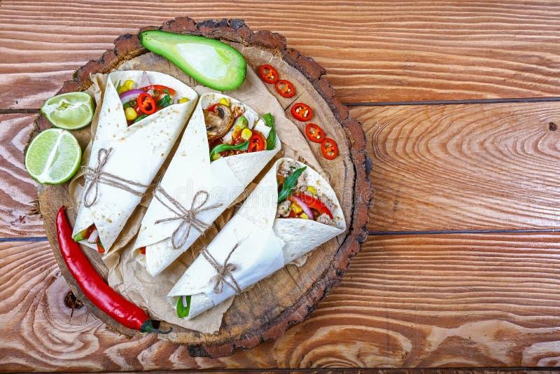 A tortilha, burritos, sanduíches torceu rolos Taco - prato tradicional da culinária mexicana Tacos mexicanos com carne, vegetais  fotos de stock royalty free