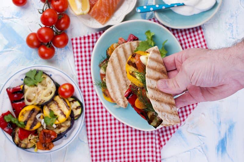 Tortilha com vegetais e salmões nas mãos masculinas Barra da aptidão dos cereais para a dieta Almoço saudável imagens de stock