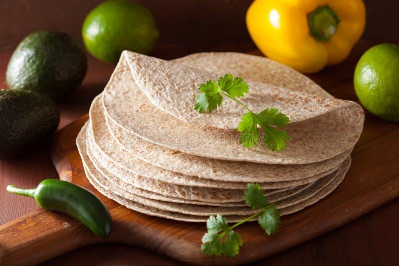 Tortilhas inteiras do trigo na placa de madeira e nos vegetais fotografia de stock royalty free