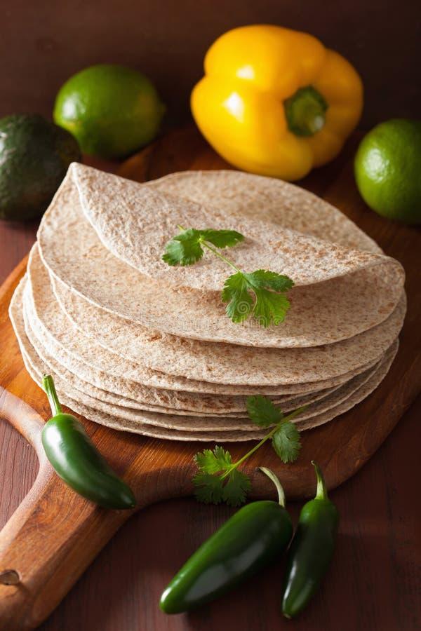 Tortilhas inteiras do trigo na placa de madeira e nos vegetais imagens de stock royalty free