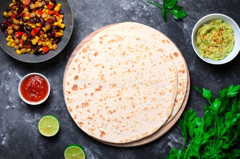 Tortilhas lisas com salsa do tomate, Guacamole e salsa fresca no fundo escuro, tortilhas do trigo, alimento mexicano imagens de stock royalty free