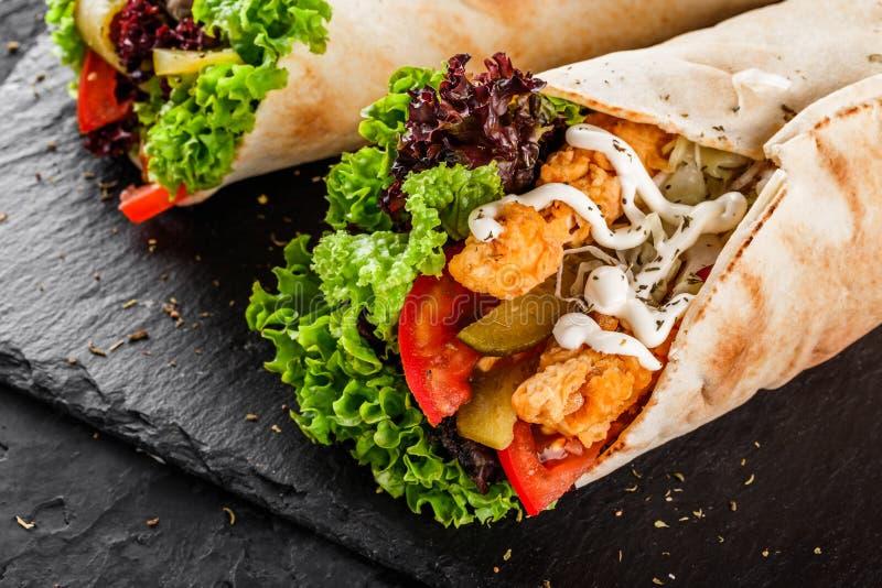 Tortilla περικαλύμματα με την ψημένη στη σχάρα λωρίδα κοτόπουλου, τα φρέσκα λαχανικά και τη σαλάτα στο μαύρο υπόβαθρο πετρών Υγιέ στοκ εικόνα