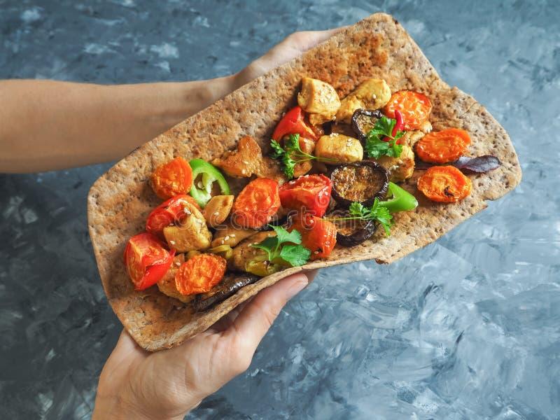 Tortilla с овощами и зажаренным мясом в его руках стоковые фото