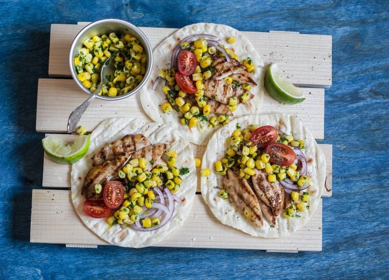 Tortilla asada a la parrilla de la salsa del pollo y del maíz en un tablero de madera en fondo azul Visión superior foto de archivo