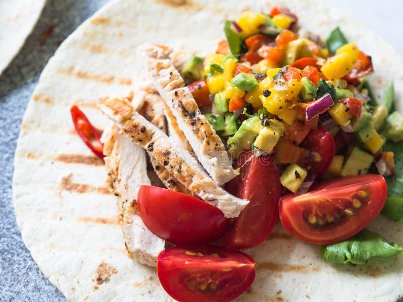 Tortilla avec le filet de poulet, la sauce à mangue de Salsa et les tomates grillés sur le fond gris Concept des Caraïbes de cuis photo libre de droits