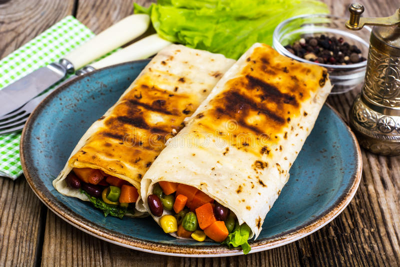 Tortilla avec le mélange végétal du plat bleu photos stock