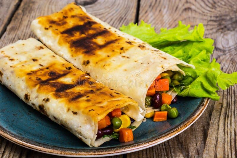 Tortilla avec le mélange végétal du plat bleu photographie stock