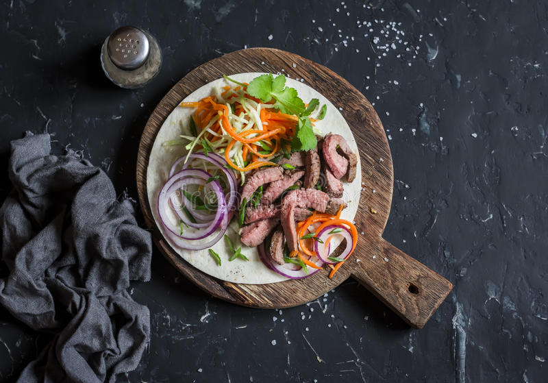 Tortilla with beef steak, marinated carrots and cabbage. Delicious lunch snack. On a dark background stock images