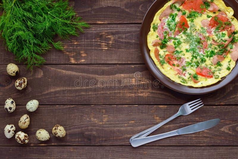 Tortilla con la salchicha y tomates e hierbas frescos foto de archivo libre de regalías