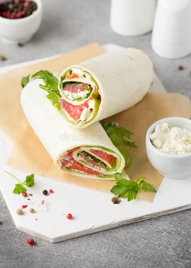 Tortilla con los salmones, la lechuga y el queso cremoso Abrigos deliciosos del bocado con los pescados y la ensalada Burrito san imagen de archivo