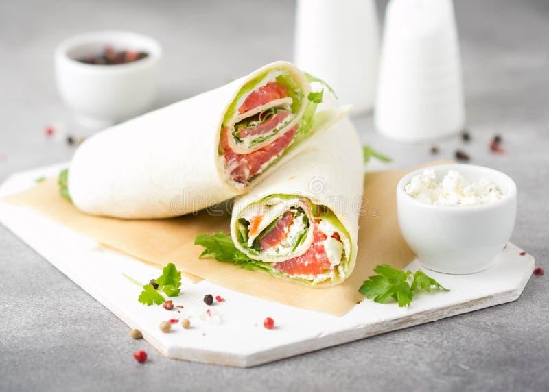 Tortilla con los salmones, la lechuga y el queso cremoso Abrigos deliciosos del bocado con los pescados y la ensalada Burrito san imágenes de archivo libres de regalías