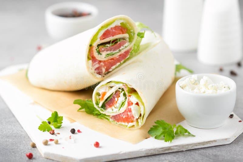 Tortilla con los salmones, la lechuga y el queso cremoso Abrigos deliciosos del bocado con los pescados y la ensalada Burrito san fotografía de archivo