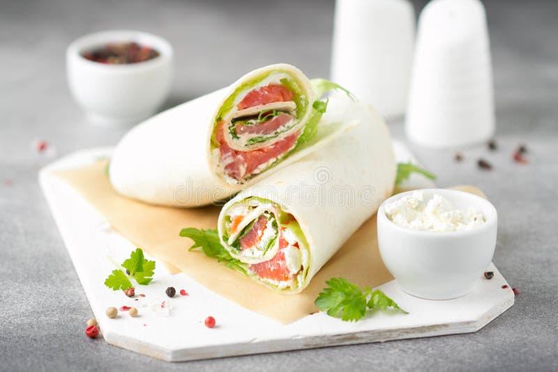 Tortilla con los salmones, la lechuga y el queso cremoso Abrigos deliciosos del bocado con los pescados y la ensalada Burrito san fotografía de archivo libre de regalías