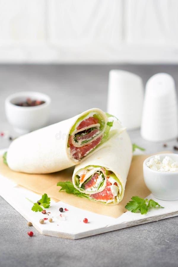 Tortilla con los salmones, la lechuga y el queso cremoso Abrigos deliciosos del bocado con los pescados y la ensalada Burrito san foto de archivo libre de regalías