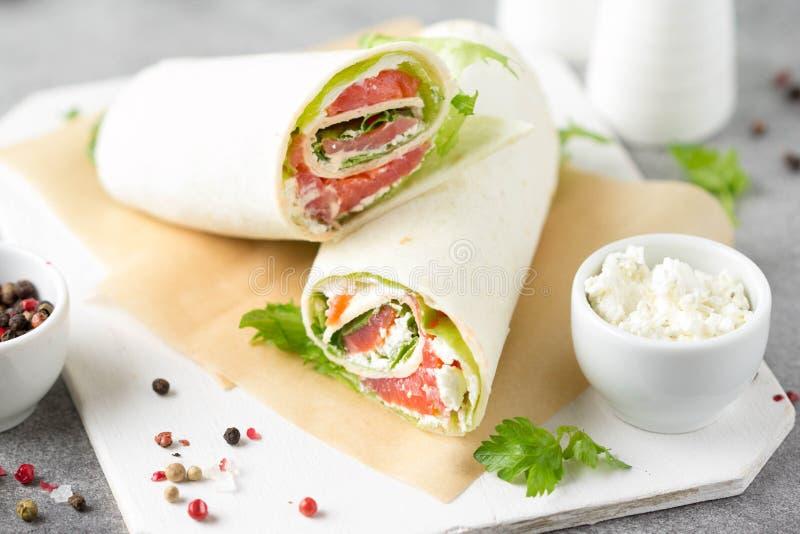 Tortilla con los salmones, la lechuga y el queso cremoso Abrigos deliciosos del bocado con los pescados y la ensalada Burrito san imagen de archivo libre de regalías