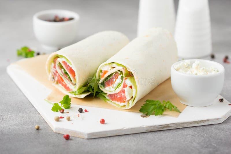 Tortilla con los salmones, la lechuga y el queso cremoso Abrigos deliciosos del bocado con los pescados y la ensalada Burrito san fotos de archivo