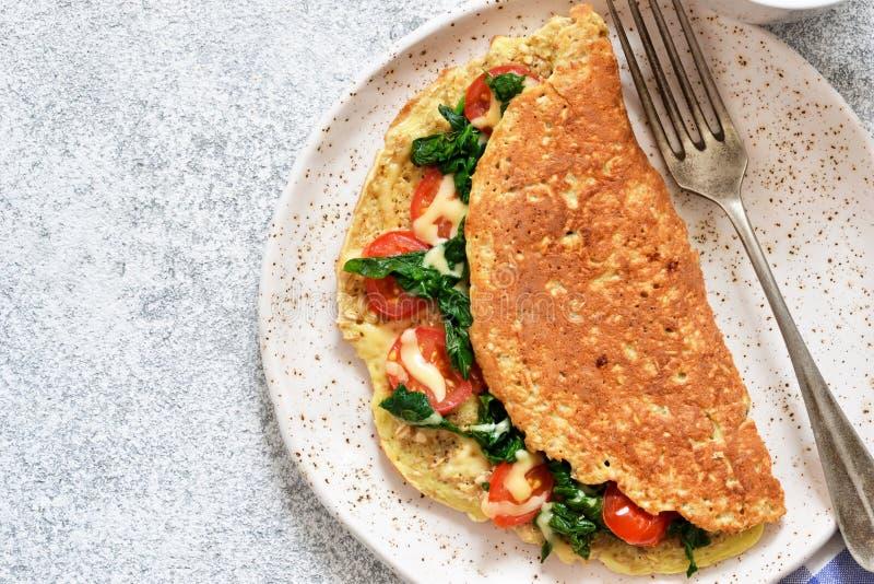 Tortilla con los tomates, el queso y la albahaca en una placa en la tabla de cocina fotografía de archivo libre de regalías