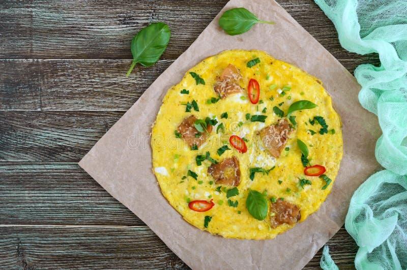 Tortilla con tocino, verdes y queso en una tabla de madera Desayuno fotografía de archivo libre de regalías