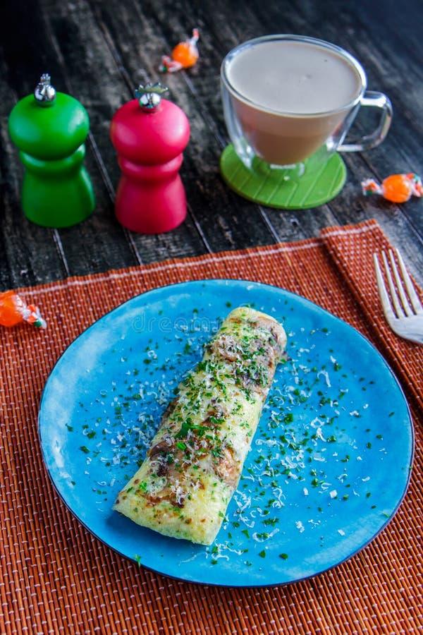 Tortilla con verdes en una placa azul y una taza de cacao imágenes de archivo libres de regalías