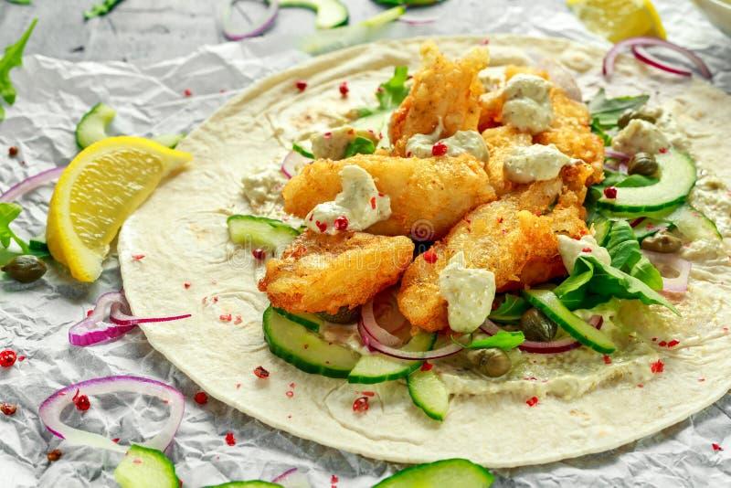 Tortilla de los pescados frescos con el pepino, la cebolla roja, las alcaparras, el limón, las hojas de la ensalada y la salsa tá fotos de archivo libres de regalías