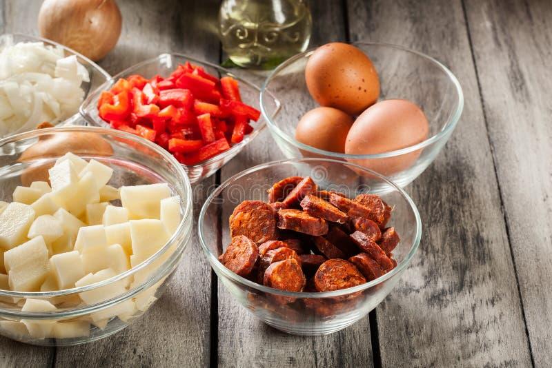 Tortilla de patatas Ingredientes para preparar la tortilla española con el chorizo, las patatas, la paprika y el huevo de la salc fotografía de archivo libre de regalías