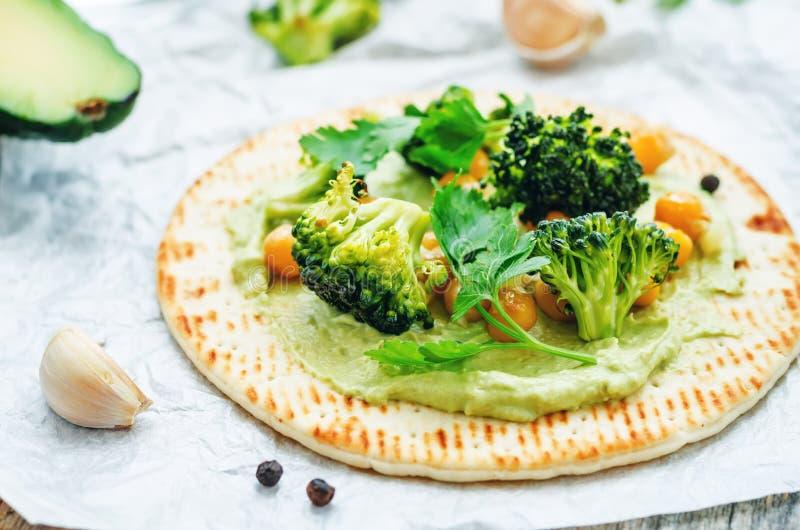 Tortilla del vegano con el bróculi y garbanzos y aguacate asados s fotos de archivo