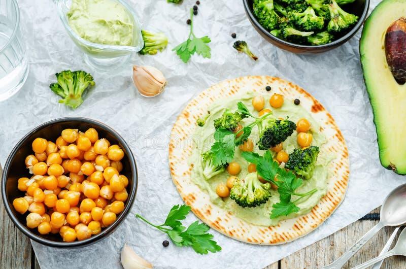 Tortilla del vegano con el bróculi y garbanzos y aguacate asados s imagen de archivo libre de regalías