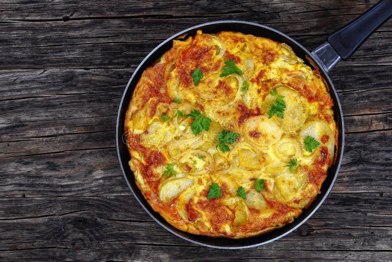 Tortilla espagnole dans la poêle sur la table image stock