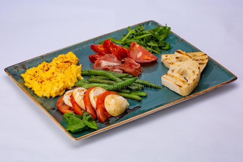 Tortilla italiana del bocado con aspagagus, el tomate, el arugula, el salami, el prosciutto y la tostada fotografía de archivo libre de regalías