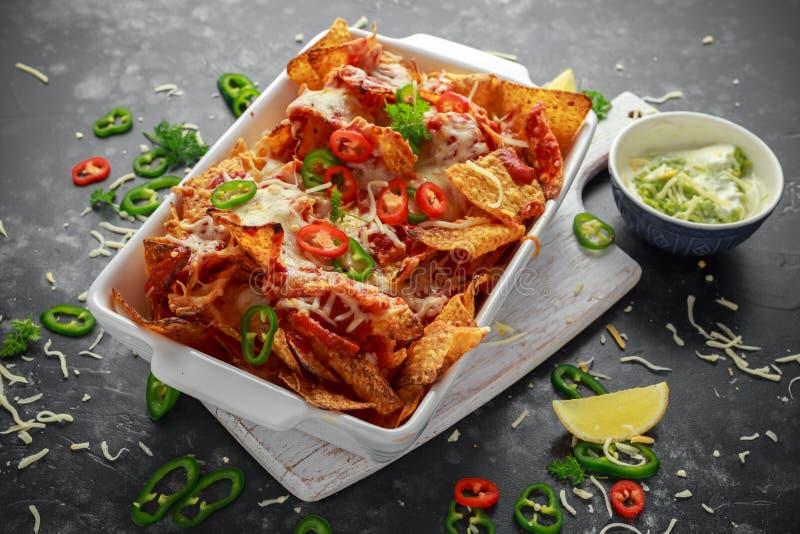 Tortilla maxican-ύφους τα τσιπ nachos που ολοκληρώθηκαν με το salsa ντοματών, τεμαχισμένα τσίλι και λείωσαν το τυρί που εξυπηρετή στοκ φωτογραφία με δικαίωμα ελεύθερης χρήσης