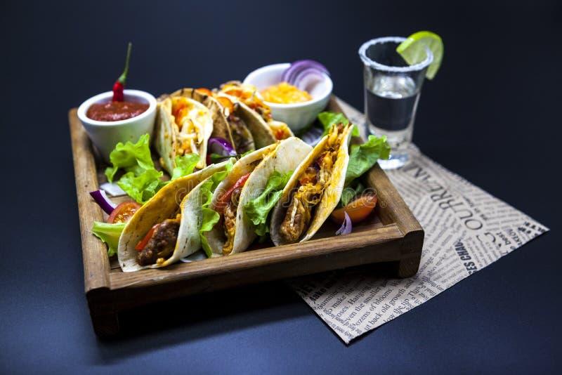Tortilla mexicaine avec de la viande, le boeuf et la sauce à légume et épicée cuite avec un tir de tequila et de chaux sur un pla photographie stock libre de droits