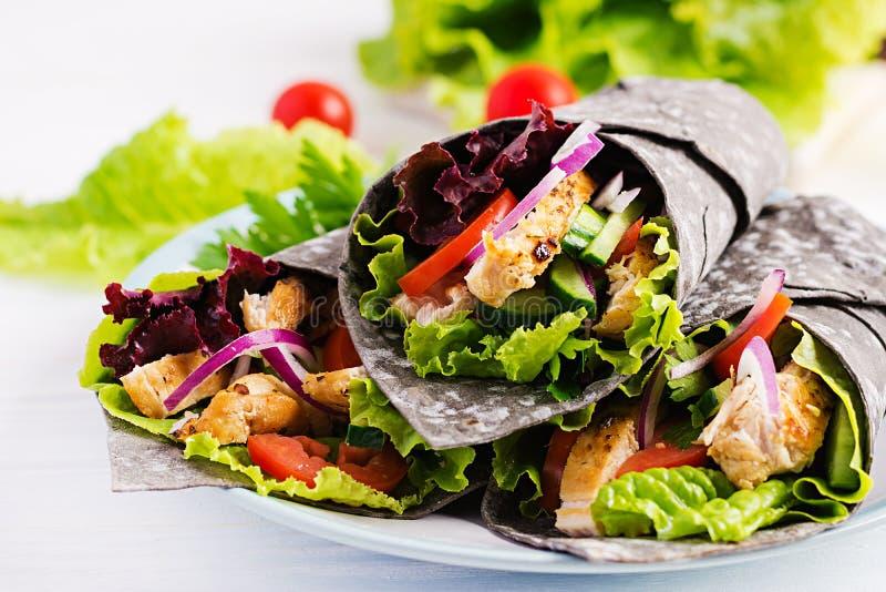 Tortilla mit zusätzlichen Tintenkopffüßerverpackungen mit Huhn und Gemüse auf weißem Hintergrund stockfoto