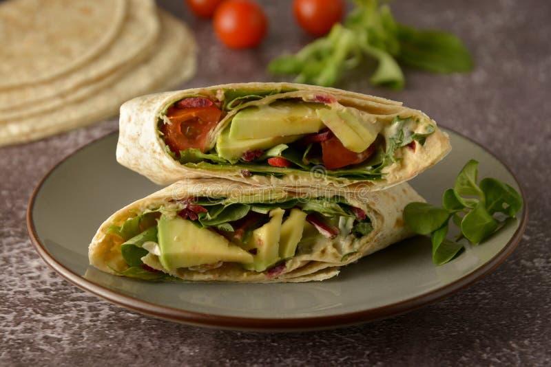 Tortilla opakunki z avocado, czereśniowy pomidor Zdrowy, weganinu jedzenie Bierze oddaloną przekąskę obraz royalty free