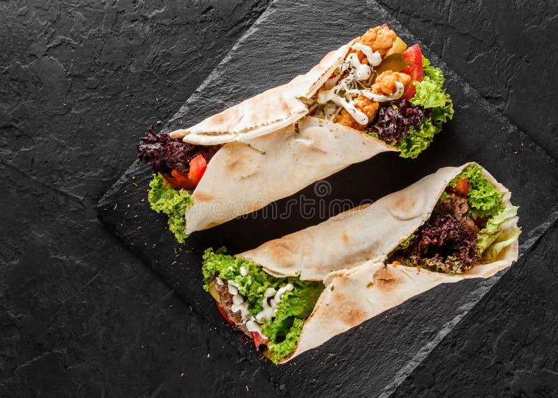 Tortilla opakunki z mi?sem, ?wie?ymi warzywami i sa?atk? na czerni piec na grillu, dryluj? t?o Zdrowa przek?ska lub oddalony lunc obrazy royalty free