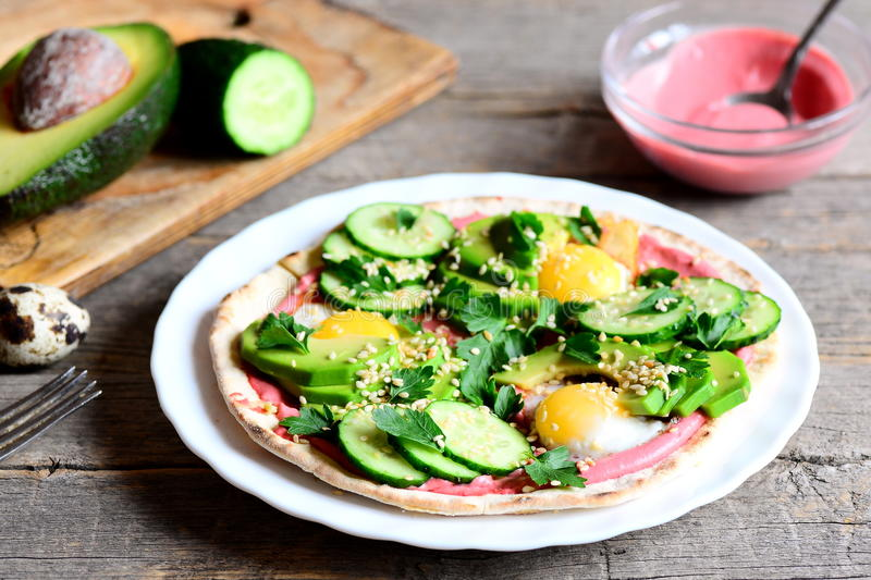 Tortilla piled high with fried quail eggs, avocado slices, cucumber, sesame and parsley and lathered with beet hummus. Avocado half, beet hummus in bowl stock photos