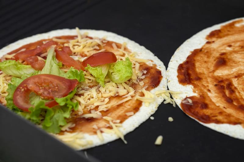 Tortilla pizza with cheese, lettuce, tomatoes. Served very hot, from grill. Concept of national food, healthy fast food royalty free stock images