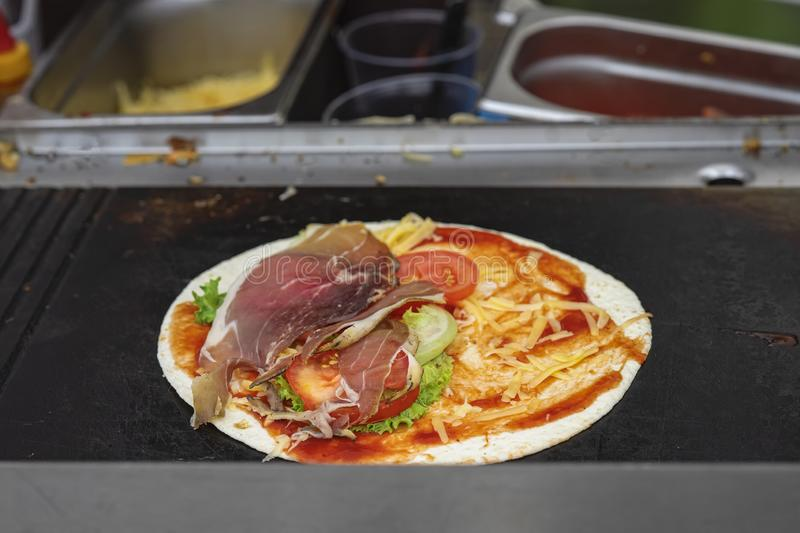 Tortilla pizza on the grill. Healthy and hearty food, fajita with grilled ham, vegetables, fresh salsa, served very hot stock image