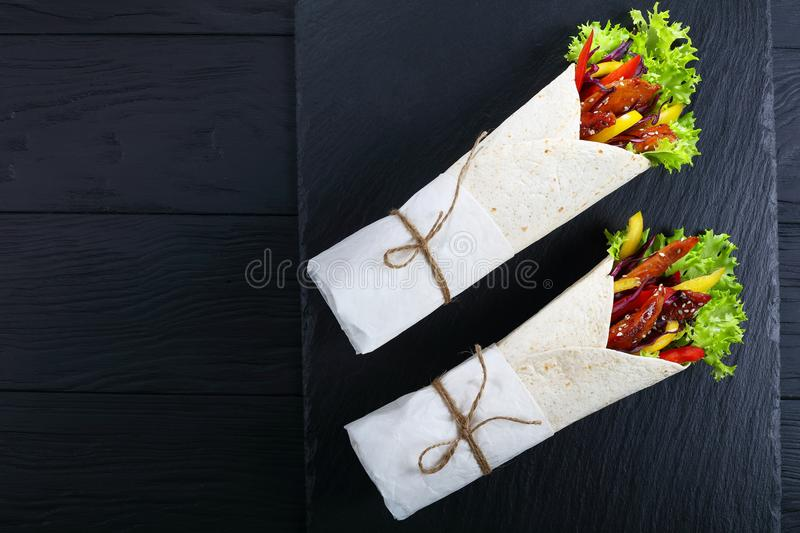 Sandwich wraps with fried chicken meats and salad. Tortilla rolled around a filling - red cabbage salad, sweet pepper strips and fried chicken meats on black royalty free stock photos