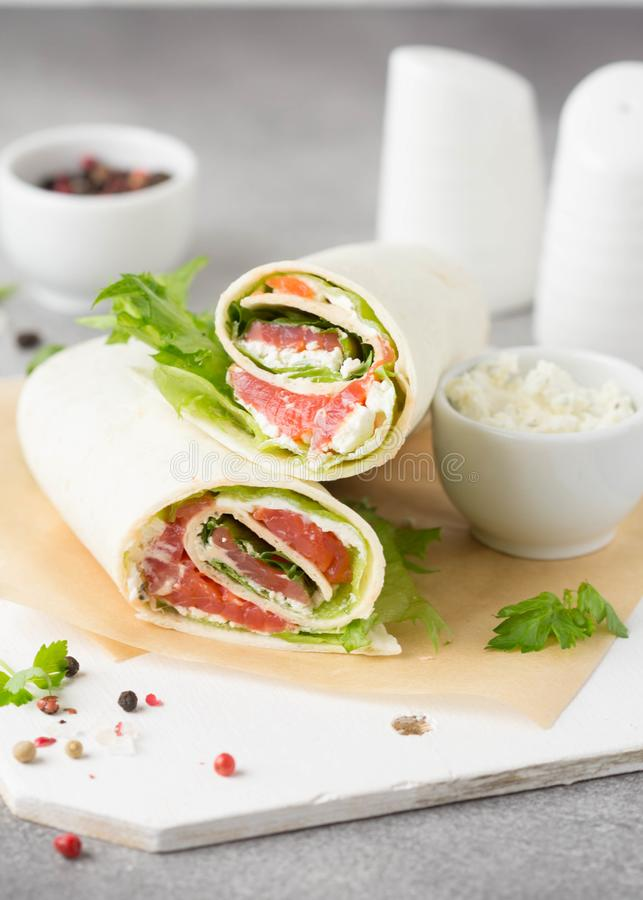 Tortilla with salmon, lettuce and cream cheese. Delicious snack wraps with fish and salad. Healthy burrito with pita bread for royalty free stock photos