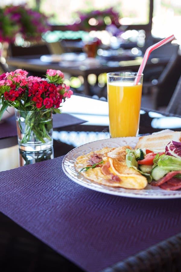Tortilla, verduras, jugo y flores en la tabla fotografía de archivo